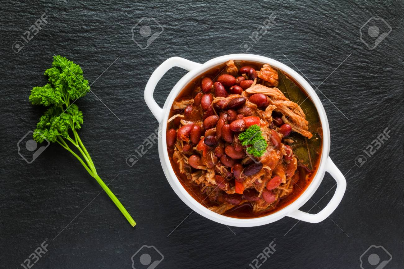 Beans with pork stewed in spicy tomato sauce with onion, paprika, beer, bell and pink pepper. White soup bowl and fresh parsley on black stone, top view. - 70570423