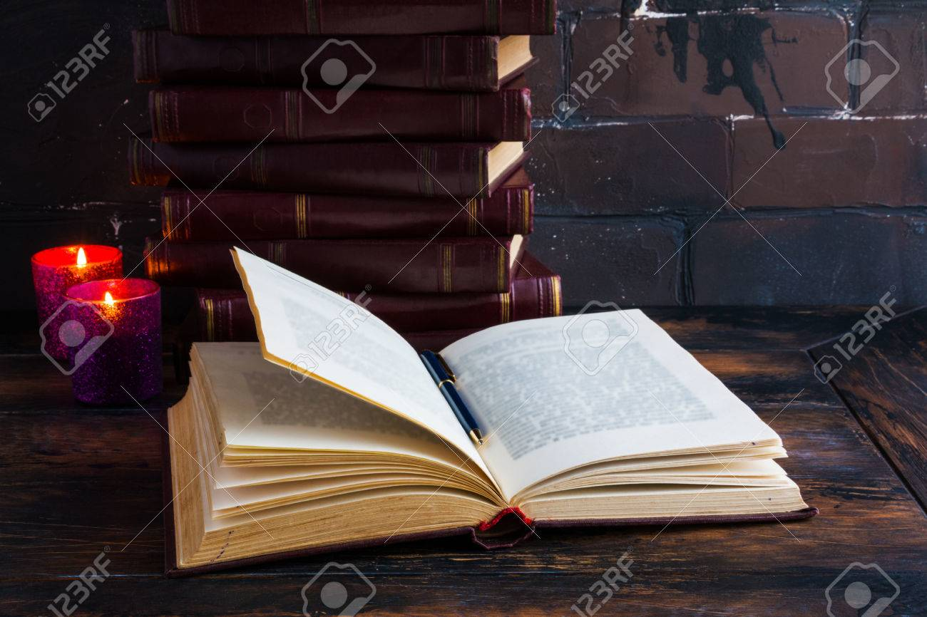 Old vintage books laying like a tower on a dark wooden table and one open book. Red hard cover, burning candle flames. - 70564595