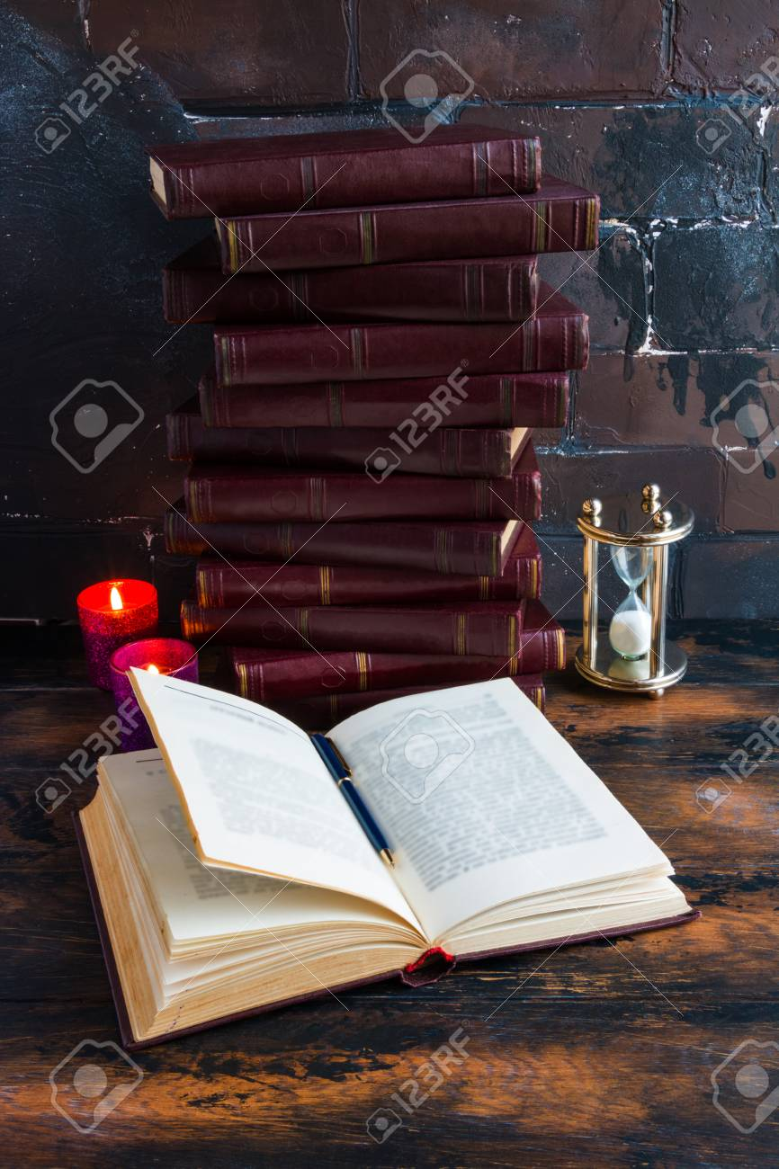 Old vintage books with red hard cover laying like a tower on a dark wooden table and one open book. Burning candle flames and hourglass. - 70615950