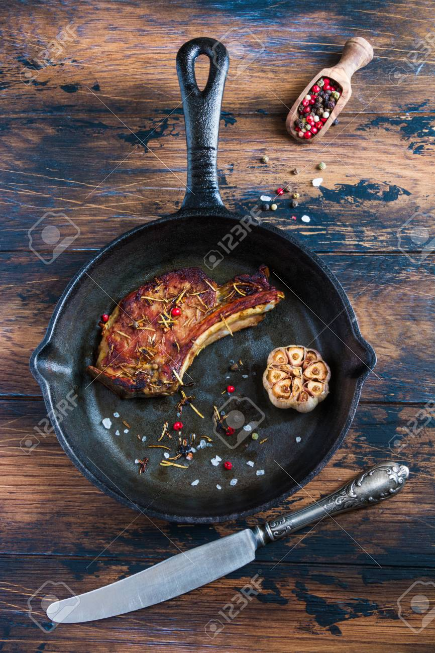 Rib eye pork steak and baked garlic in black cast-iron skillet on wooden rustic table. Red pepper, vintage knife, top view. - 70590443