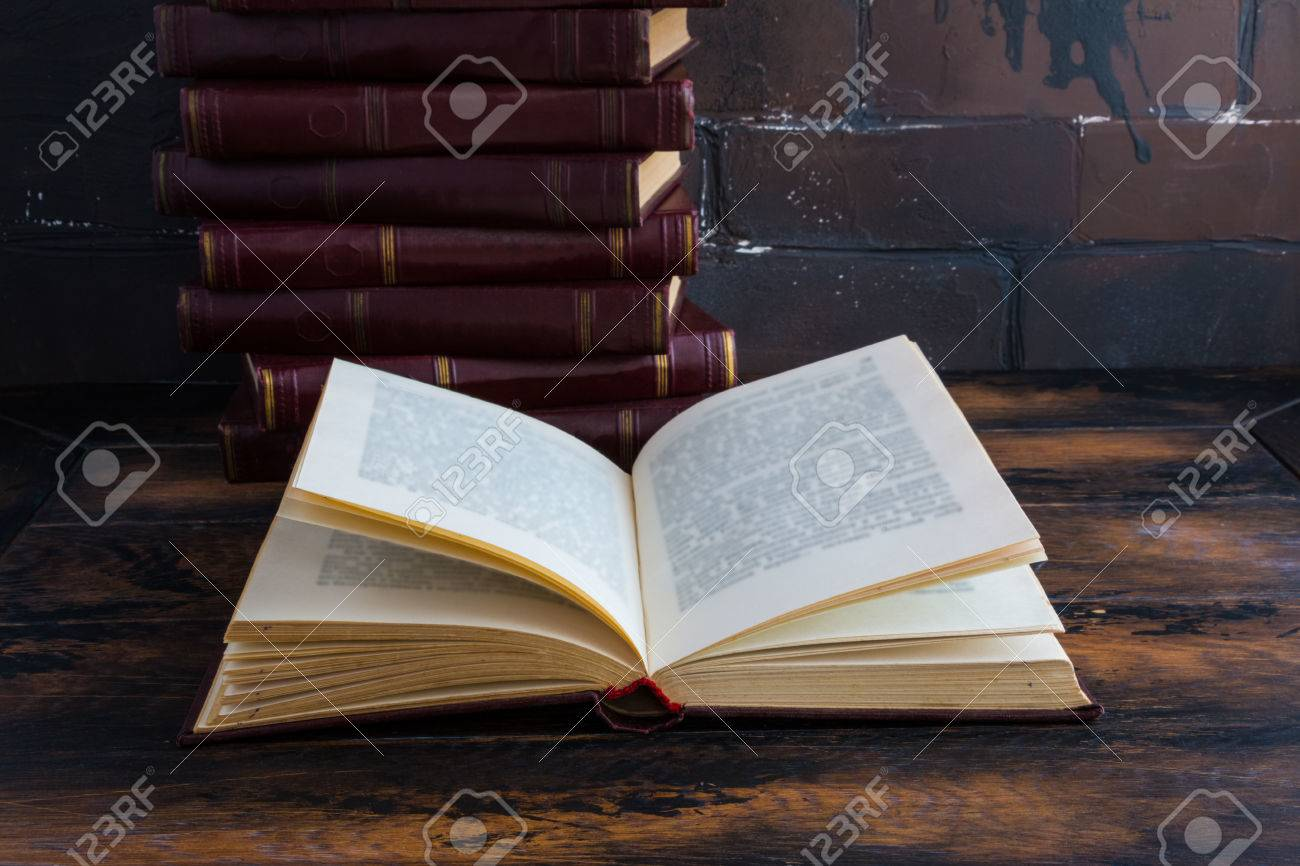 A stack of books with a dark red hard cover one another and open book on a wooden table against the background of brown brick wall behind. - 70588942