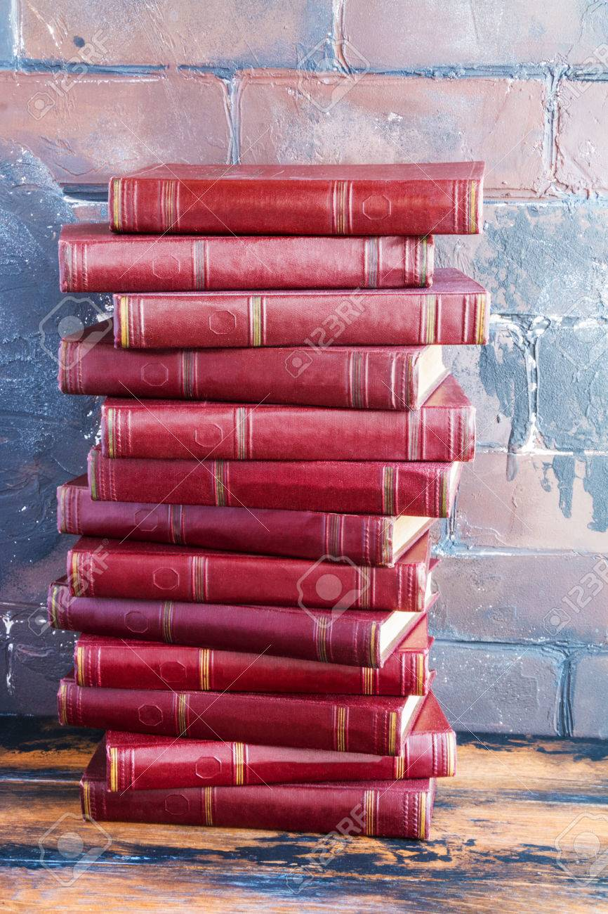 A stack of books with a dark red hard cover one another on a wooden table against the background of brown brick wall behind. - 70564600