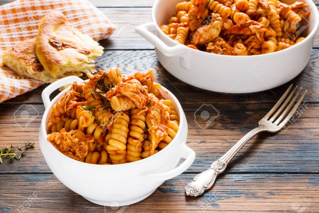 Fusilli pasta with chicken. Cooked in spicy sauce from tomatoes, onion, garlic, dried oregano and thyme, paprika and olive oil. Fresh bread, white bowl and casserole on wooden brown rustic table. - 70589875