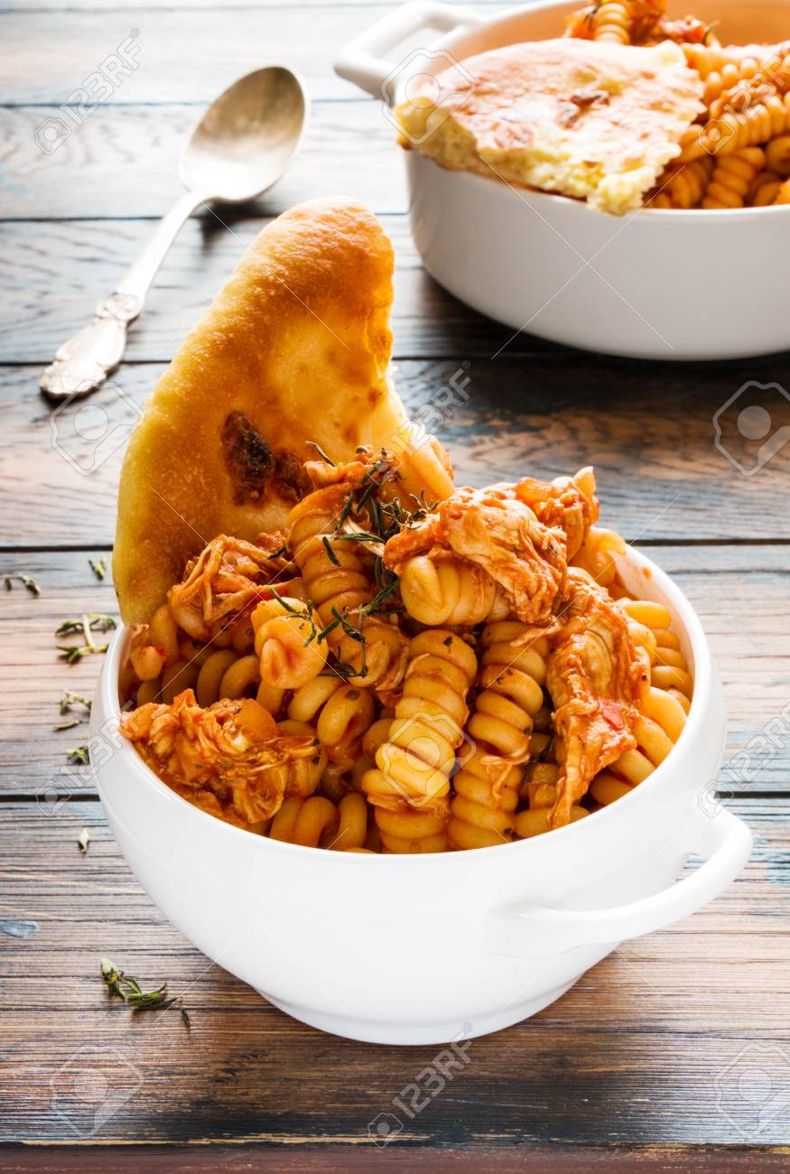 Fusilli pasta with chicken. Cooked in spicy sauce from tomatoes, onion, garlic, dried oregano and thyme, paprika and olive oil. Fresh bread, white bowl and casserole on wooden brown rustic table. - 70588955