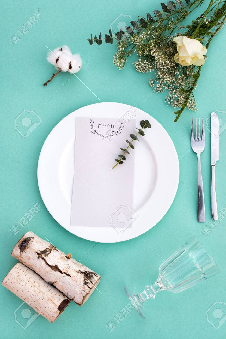 Dinner menu for a wedding or luxury evening meal. Table setting from above. Elegant empty plate, cutlery, glass and flowers. - 52600838