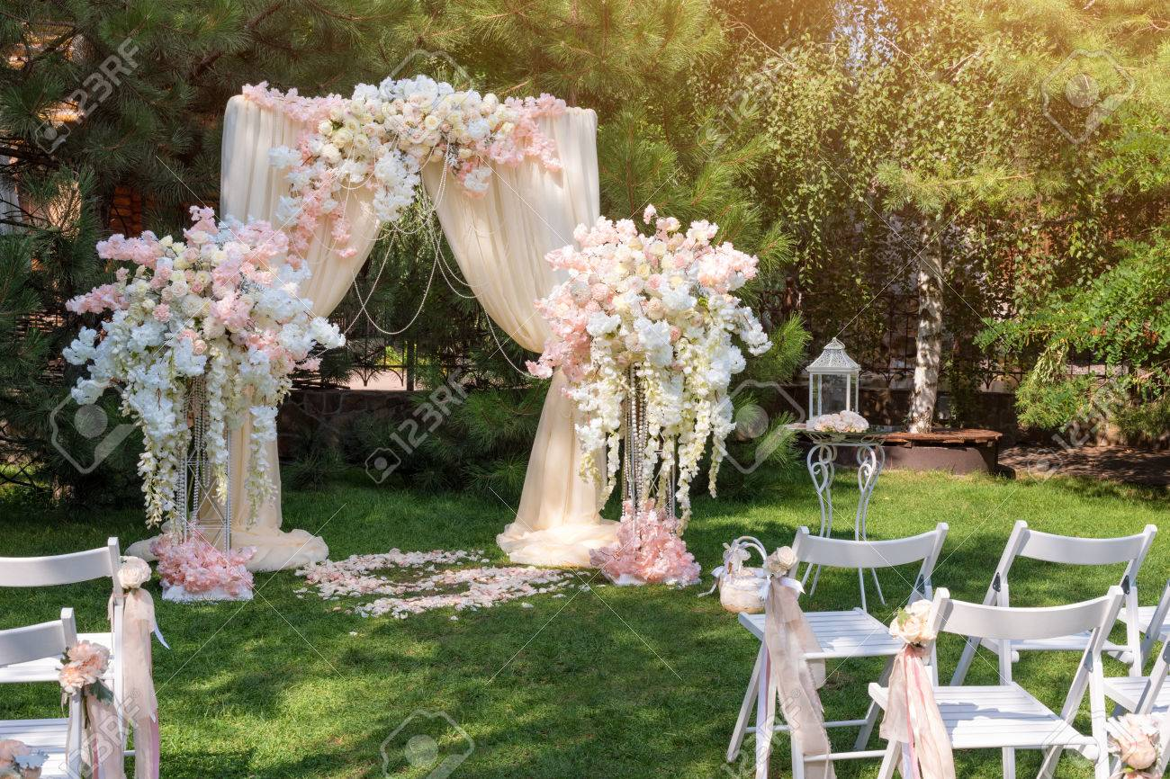 Wedding arch decorated with cloth and flowers outdoors beautiful stock photo wedding arch decorated with cloth and flowers outdoors beautiful wedding set up wedding ceremony on green lawn in the garden junglespirit Gallery