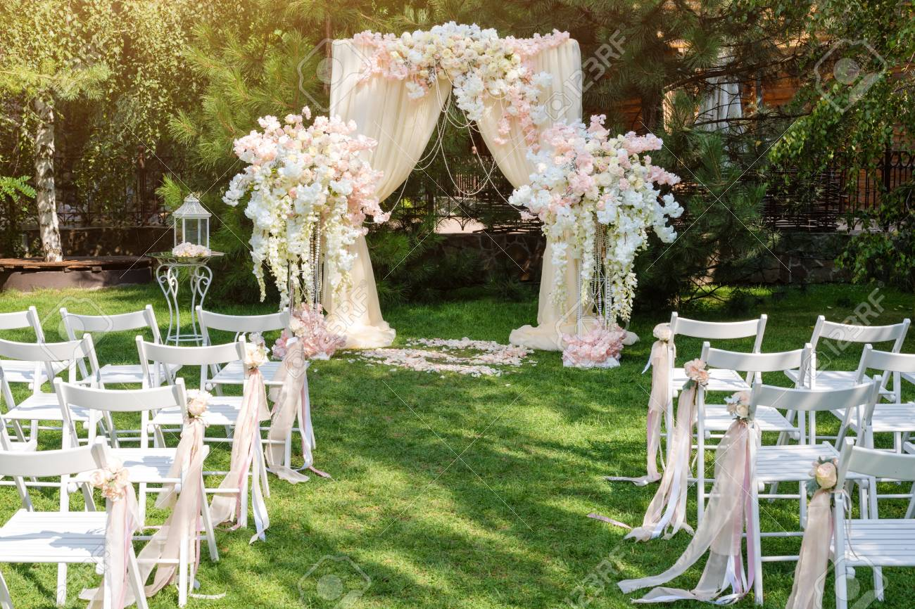 Wedding arch decorated with cloth and flowers outdoors beautiful stock photo wedding arch decorated with cloth and flowers outdoors beautiful wedding set up wedding ceremony on green lawn in the garden junglespirit Images