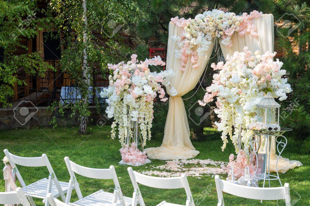 Wedding arch decorated with cloth and flowers outdoors beautiful stock photo wedding arch decorated with cloth and flowers outdoors beautiful wedding set up wedding ceremony on green lawn in the garden junglespirit