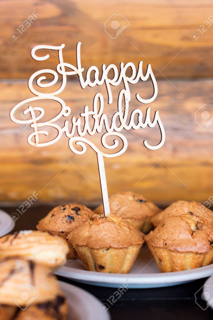 Birthday Cakes And Muffins With Wooden Greeting Sign On Rustic Background Sing Letters