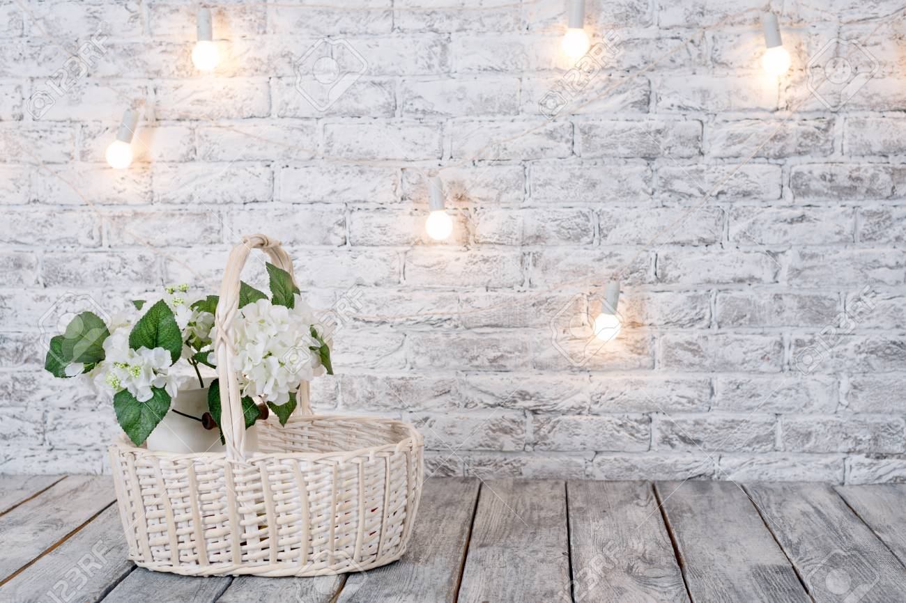 Flowers In Basket With Light Bulbs On White Brick Background Stock