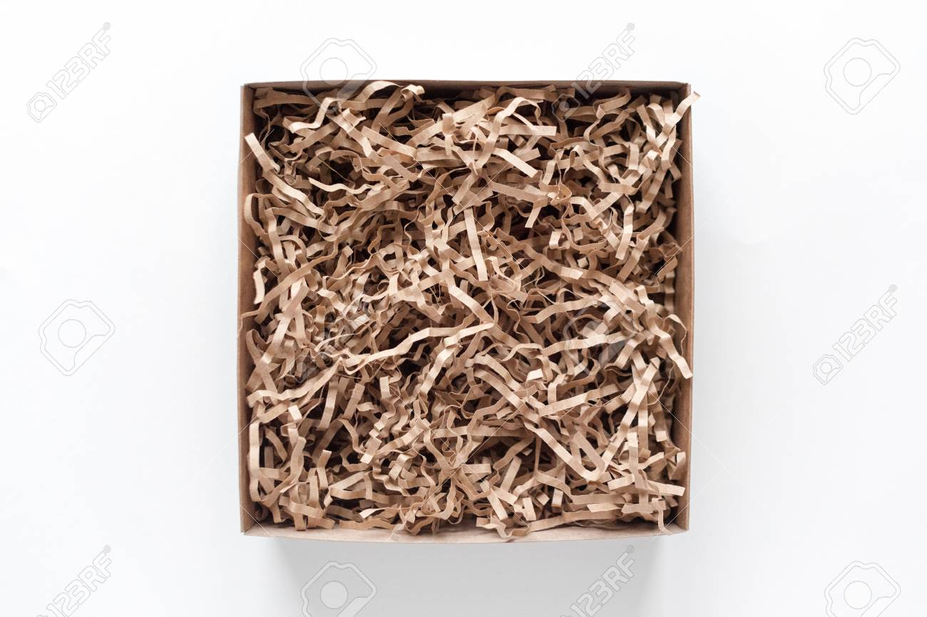 Opened gift box with decorative straws fillers on light background. Brown craft paper box for