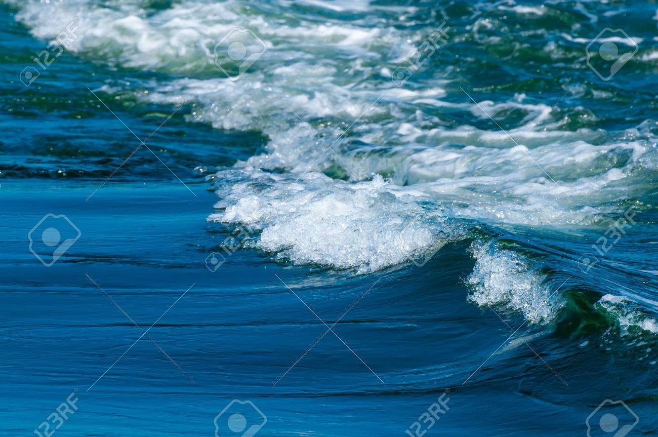Small waves breaking on the beach in close-up