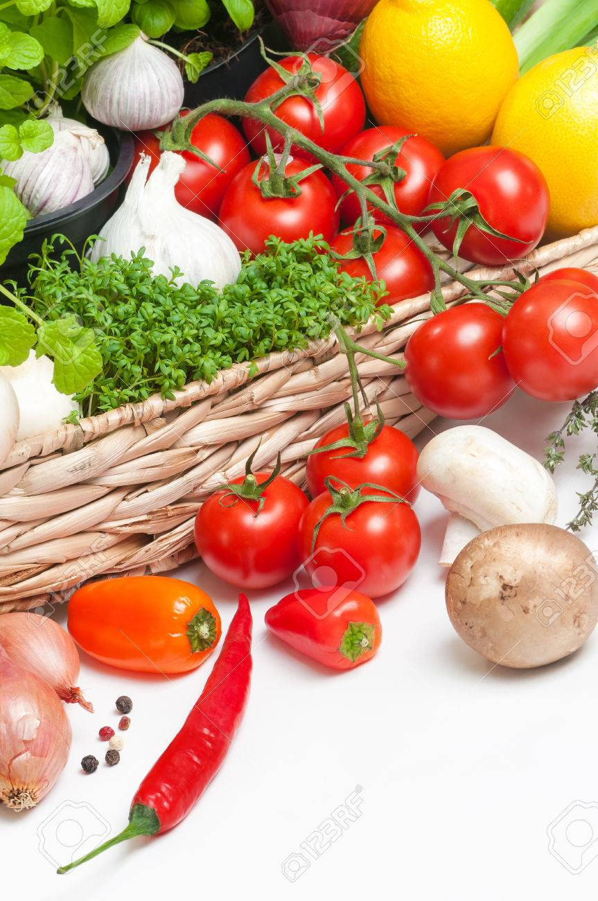 Fresh vegetables and aromatic herbs in raffia basket on white