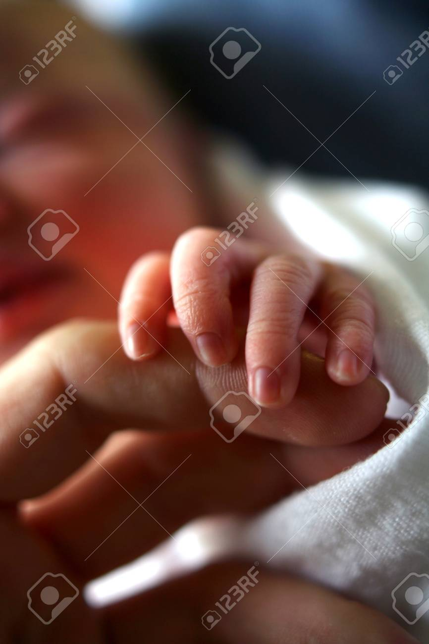 Close up of a baby gripping adult's finger Stock Photo - 9378780