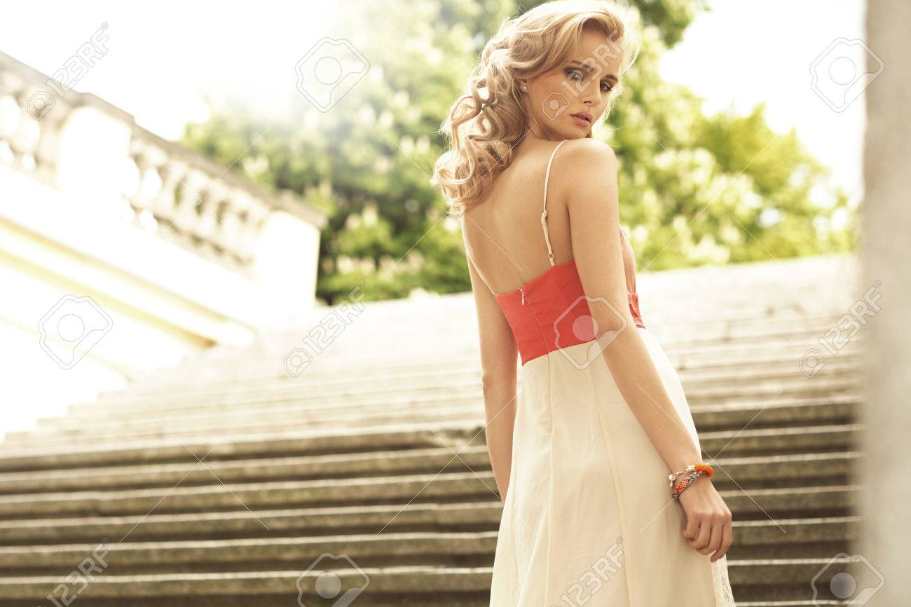 Elegant young woman on the antique stairs - 30354098