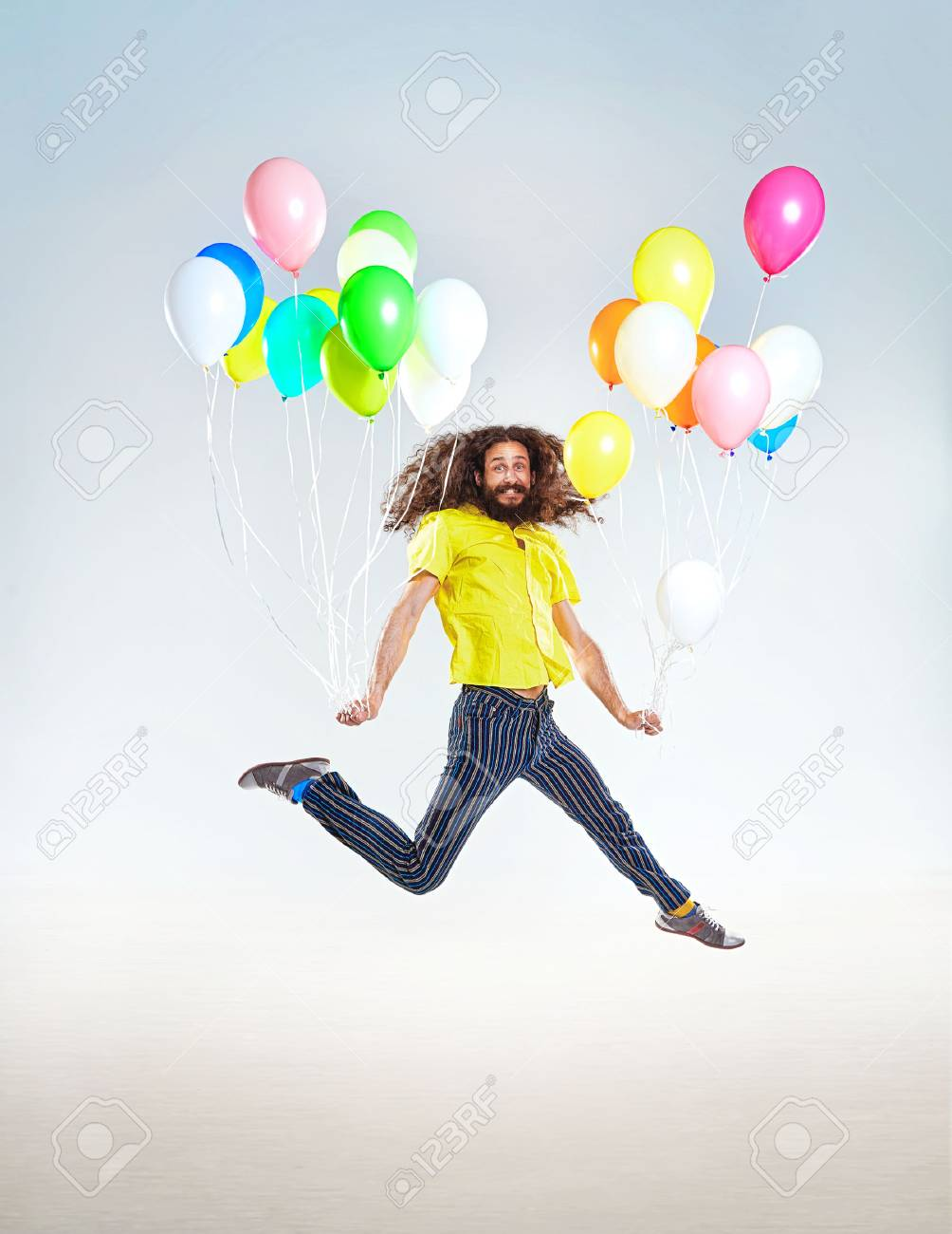 Conceptual portrait of a childish guy jumping with balloons - 85169983