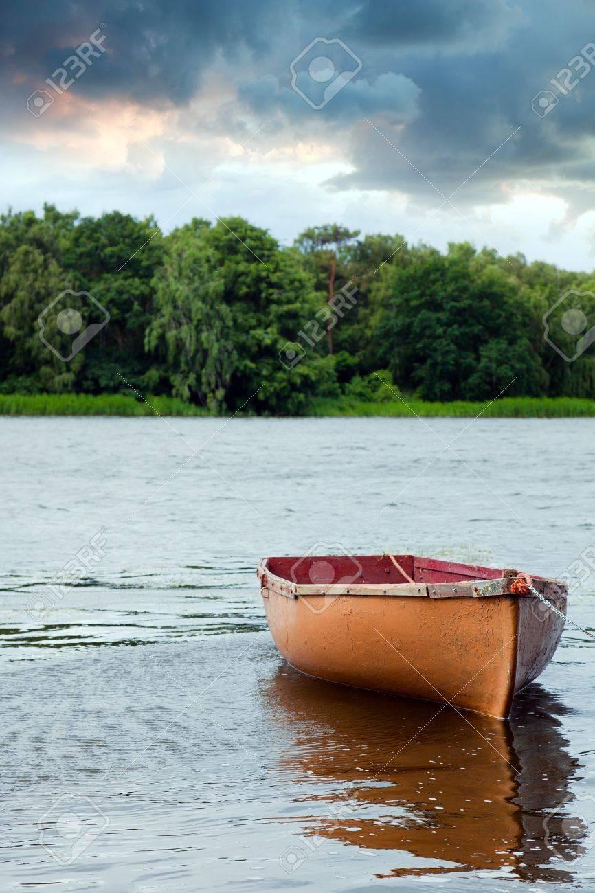 Lone fishing boat floating on the lake Stock Photo - 9945791