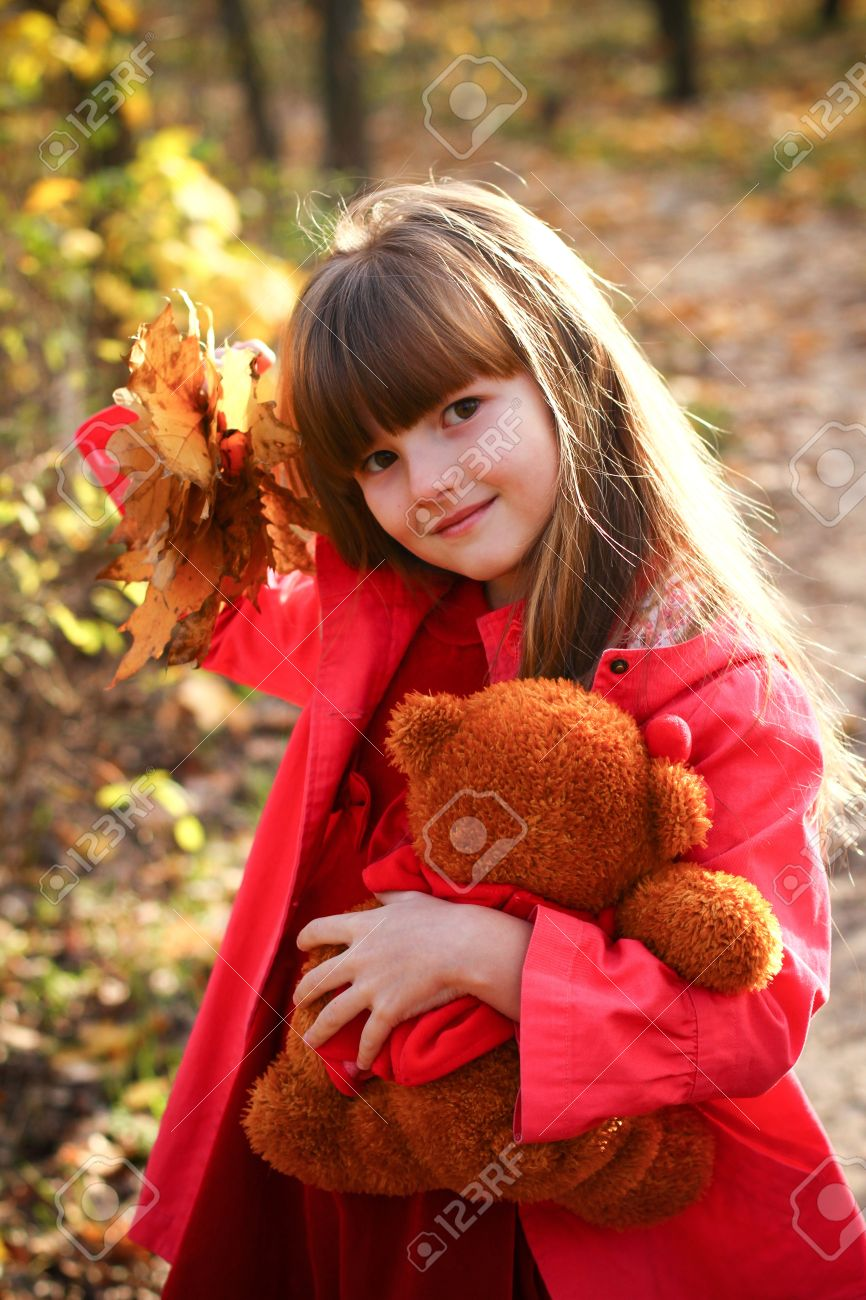 sweet little girl in the autumn forest holding maple leaves and