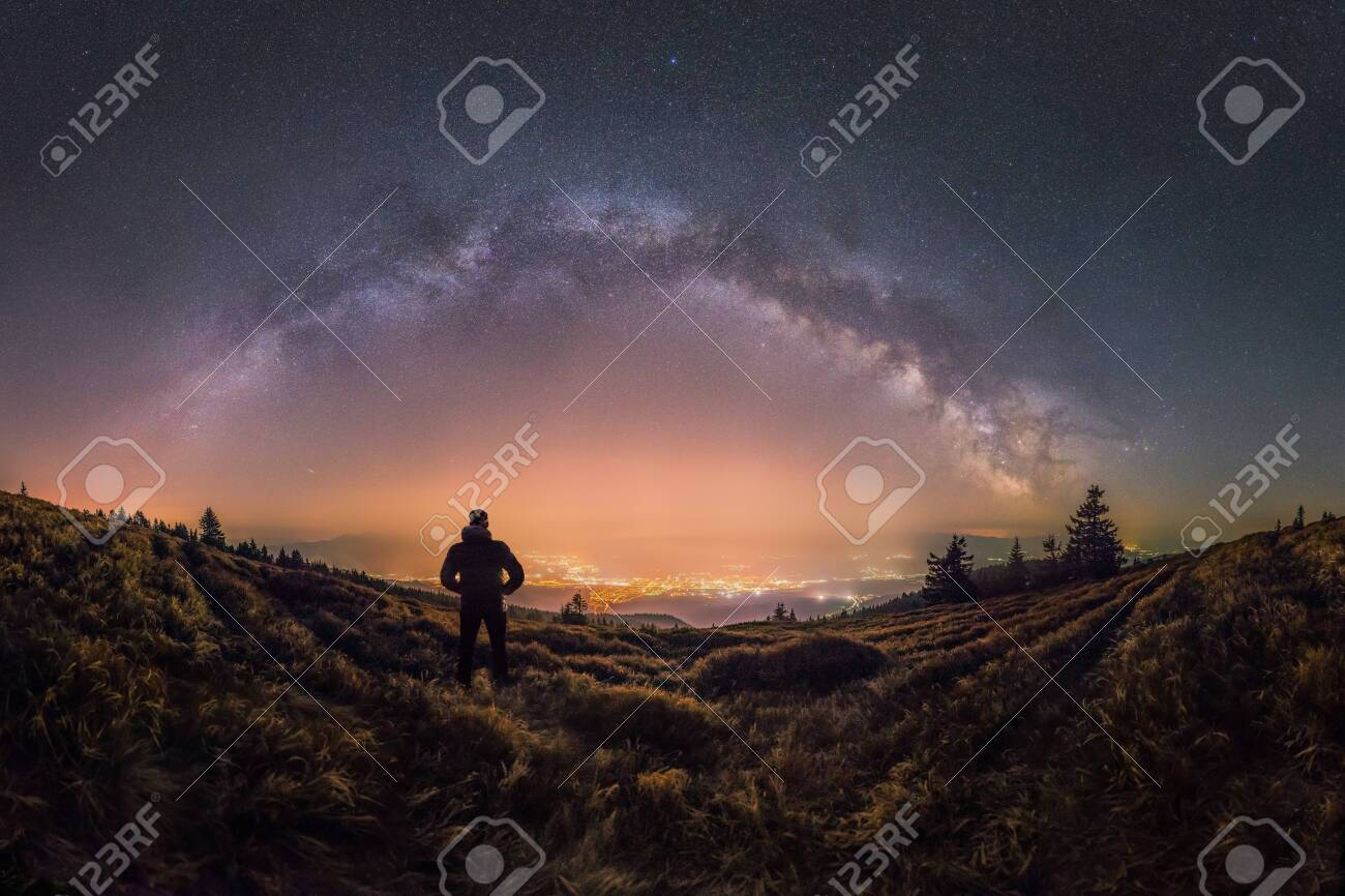 Person looks at the city and Milky Way glowing in the sky - 137561455
