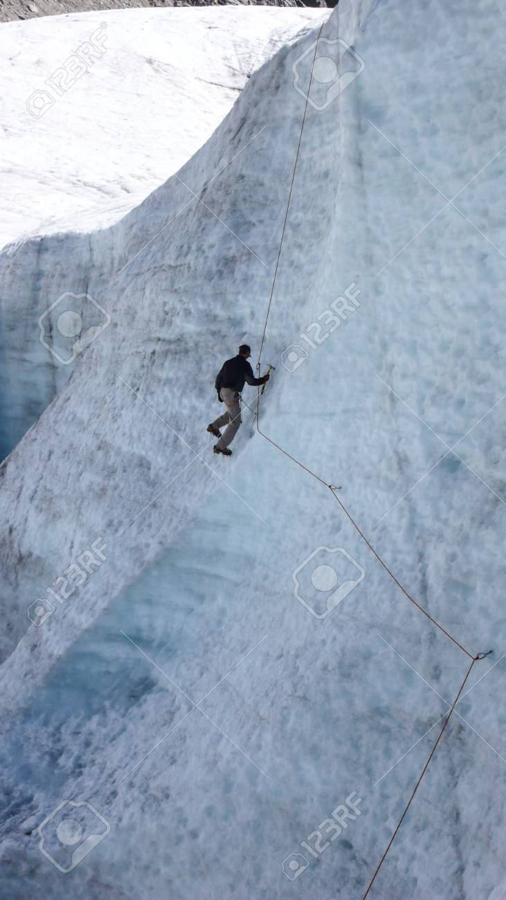 young male mountain guide candidate training ice axe and rope