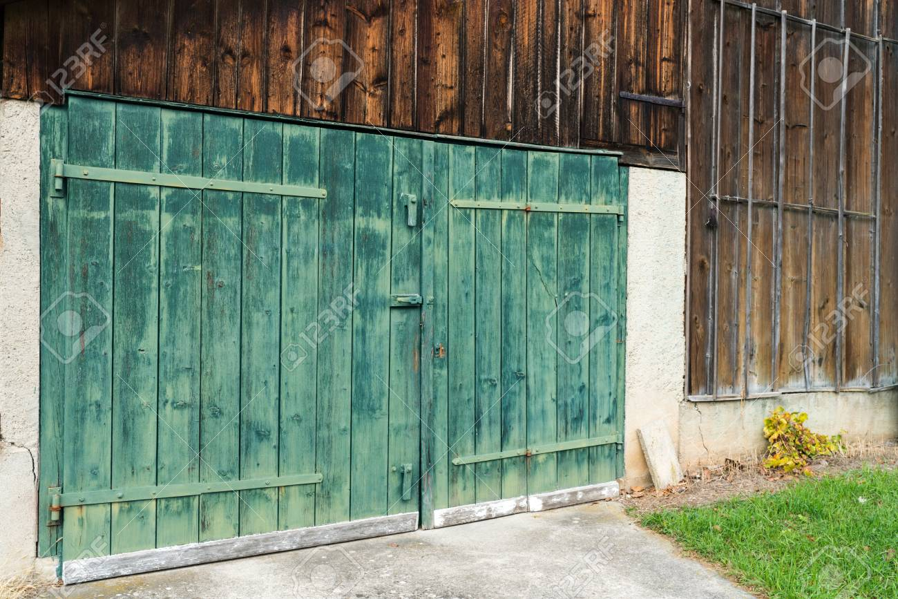 Background View Of An Old Vintage Rustic Green Wooden Barn Door On A Wooden  Shed Stock