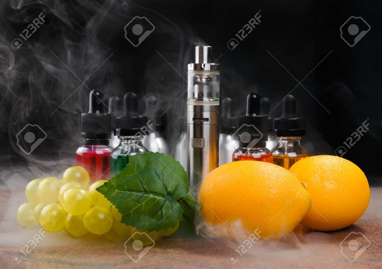 Electronic cigarette, bottles with vape liquid, lemons and fake
