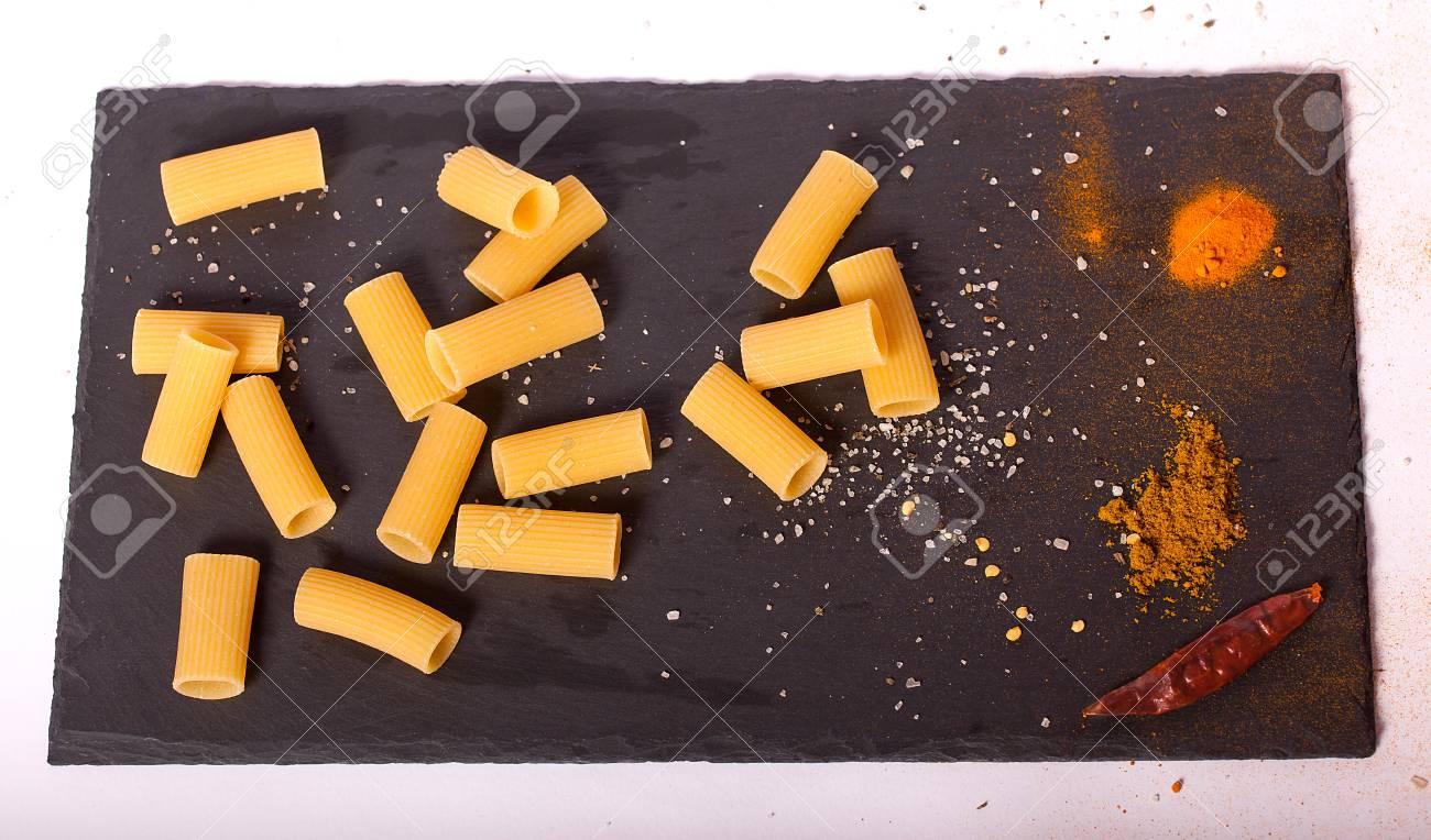 Raw macaroni close-up on a black background. - 85436505