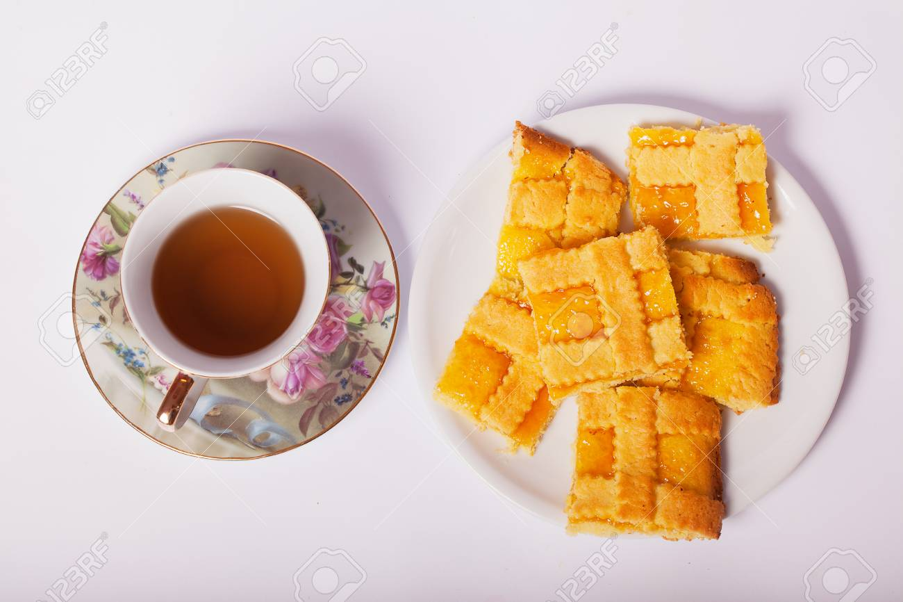 Crostata with apricot jam and a cup of tea on a white background. - 85955937