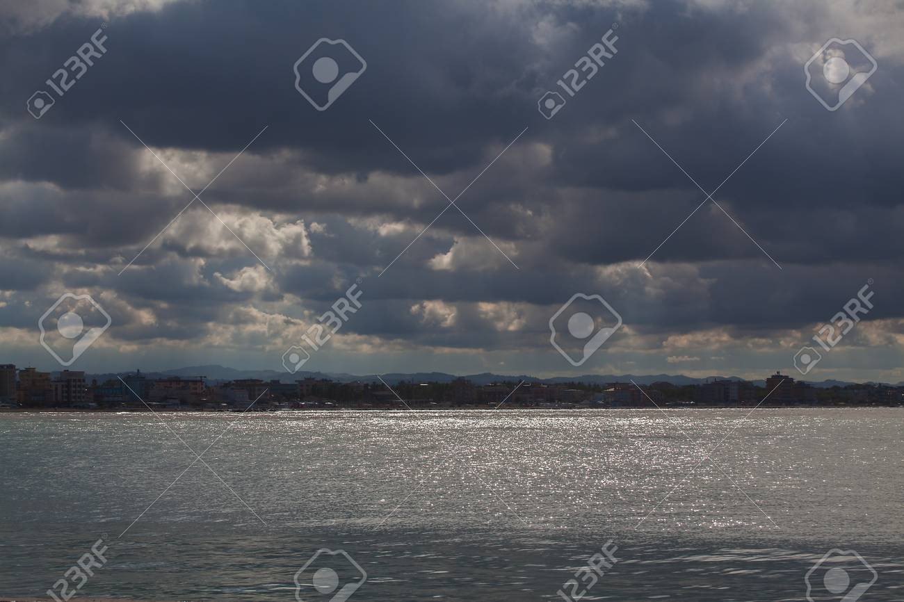 View from the sea to the coastline on a cloudy day. The sky with clouds - 87729599