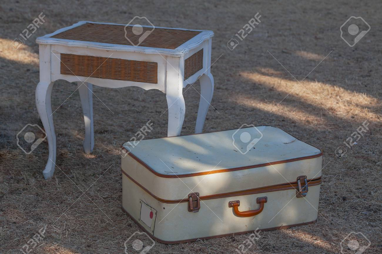 Old white suitcase on the grass and a wicker table close-up. - 89438026