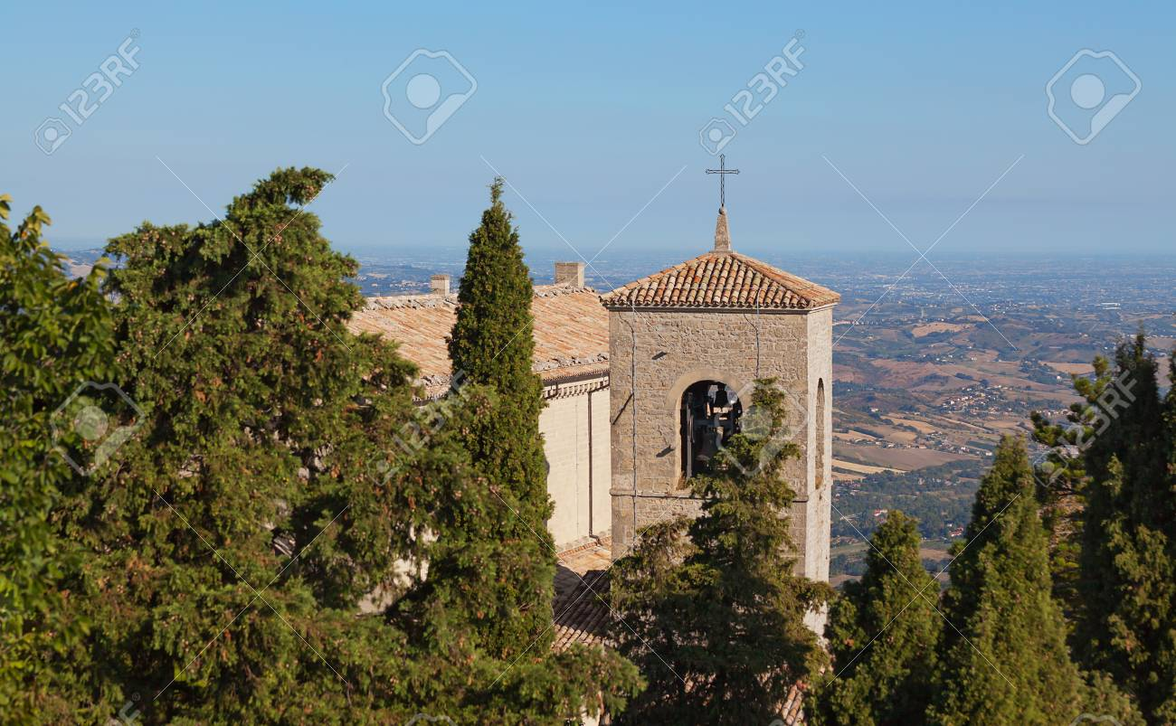 The cross on the roof of a church between the trees against the blue sky. Bell tower. - 89367926