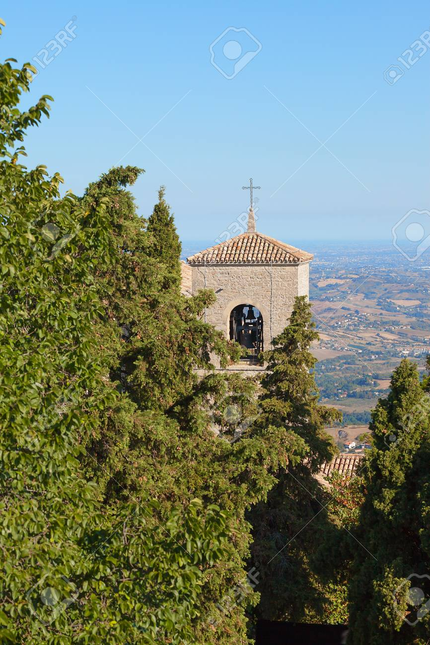 The cross on the roof of a church between the trees against the blue sky. Bell tower. - 91738651