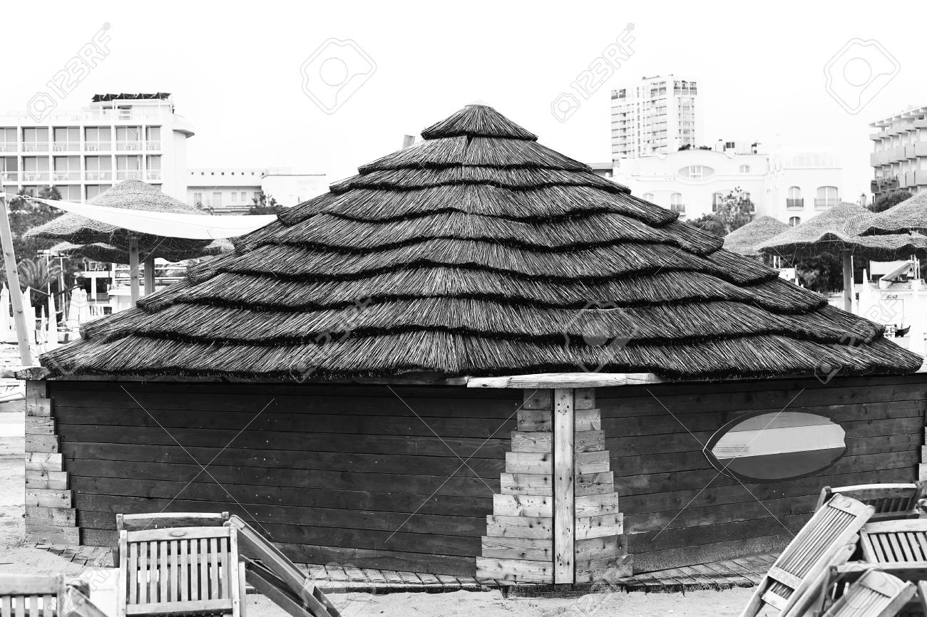 Wooden house with a reed roof on the beach. - 89942285