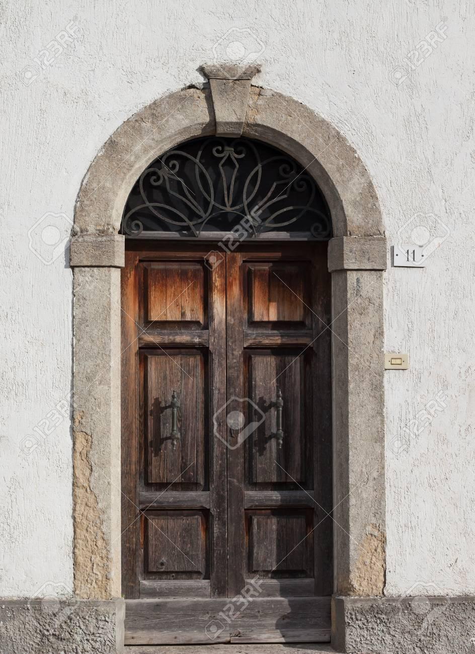 Old wooden door with beautiful metal handles close-up. - 93233800