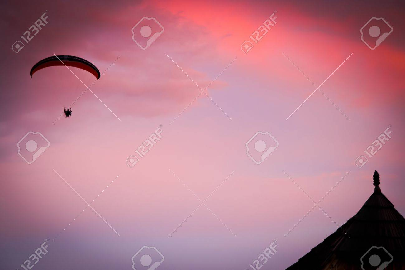 Silhouette of powered paraglide against sunset sky Stock Photo - 15491870