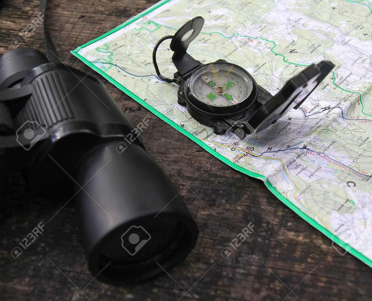Ferngläser und ein kompass auf der karte in der natur während