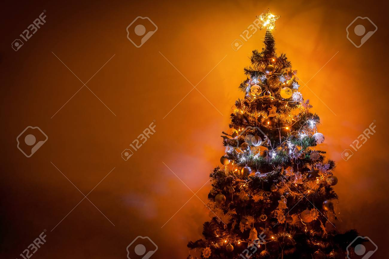 beautifully romantic decorated christmas tree with multi colored lights on warm background and space for your