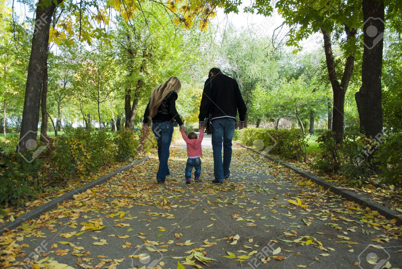 Family walk in the park with fun toys, the bright sun illuminates the faces of children and parents, and rustling leaves underfoot on the grass Stock Photo - 10836310