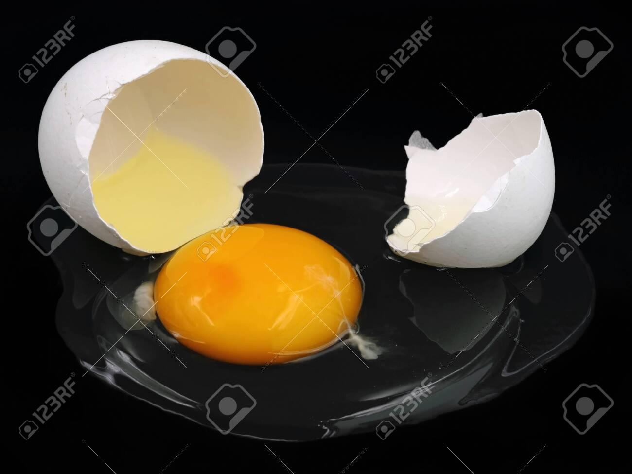 cracked white egg isolated on black background - 143611521