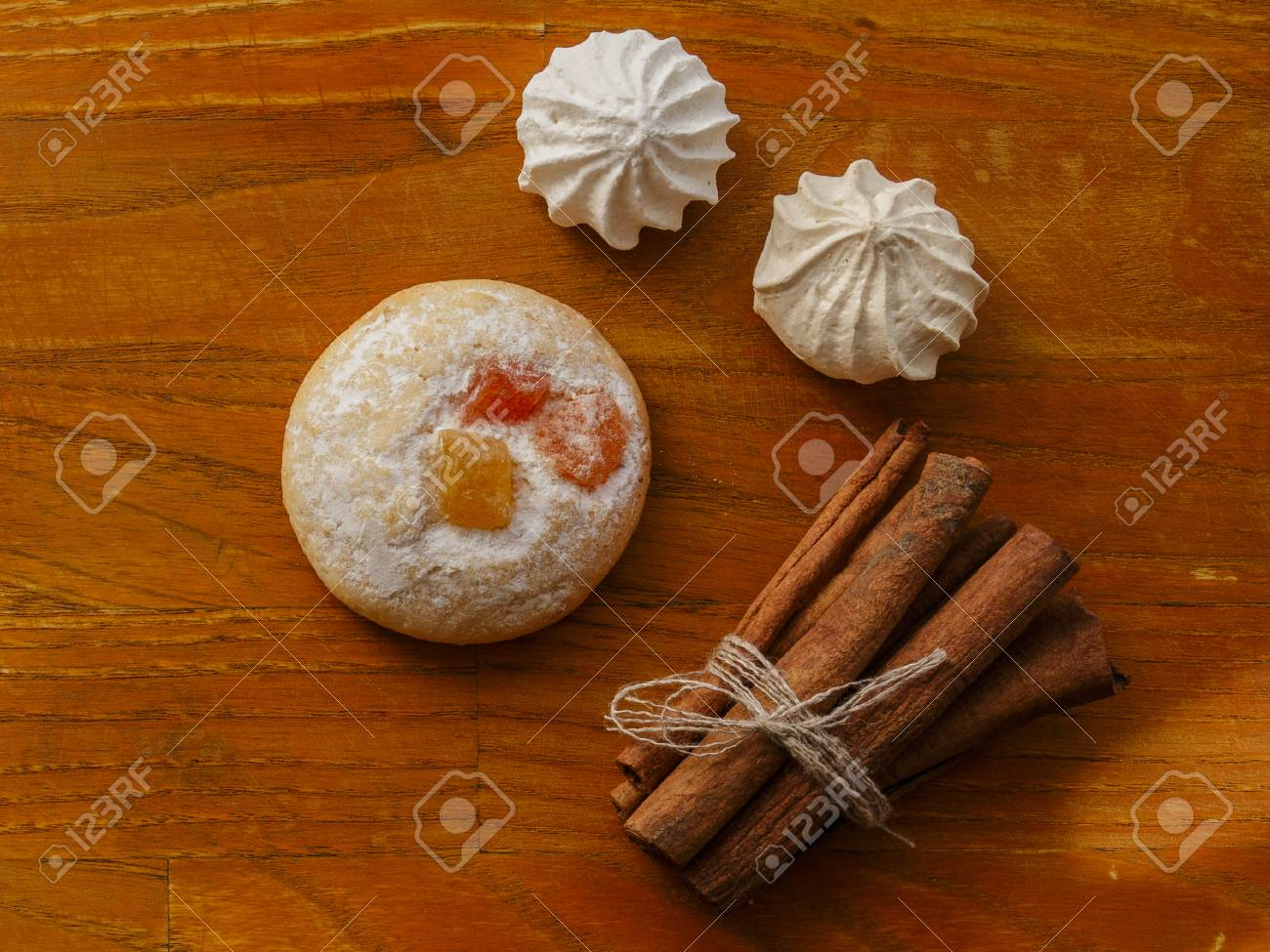 Cookie And Meringues And Cinnamon Sticks On Wooden Table Top