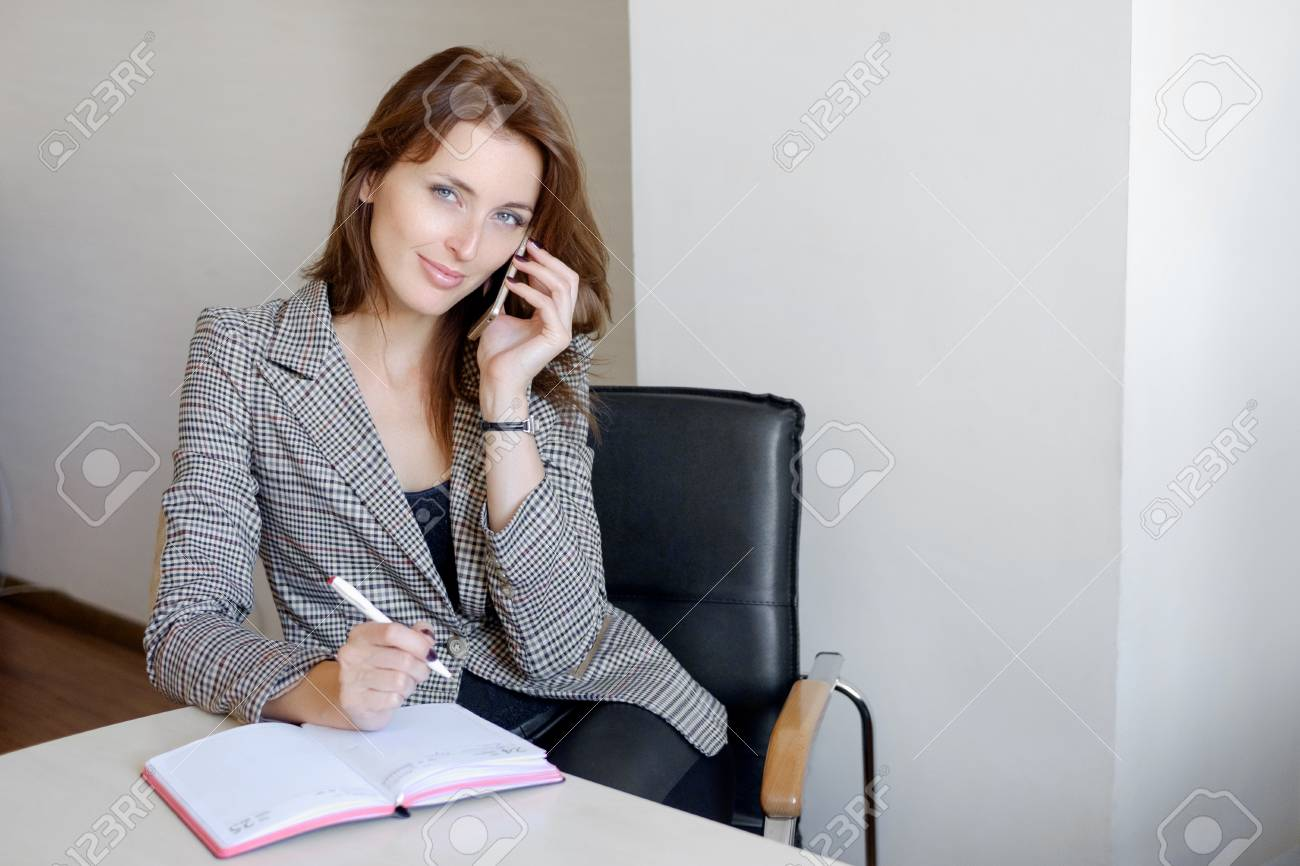 Young Happy Businesswoman Talking On The Phone And Writing Notes
