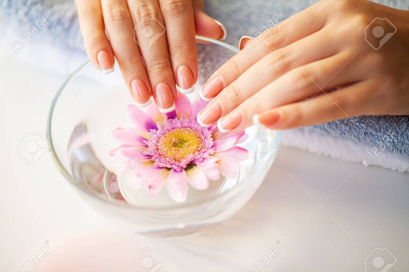 Nails care. Beautiful womans nails with french manicure, in beauty studio - 131913986