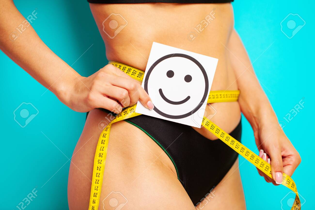Slimming concept, slender woman measures the size of her waist with a measuring tape. - 148965122