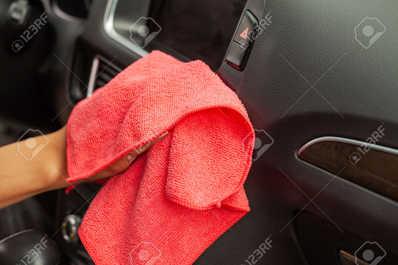 Hand with microfiber cloth cleaning Interior modern car. - 165414991