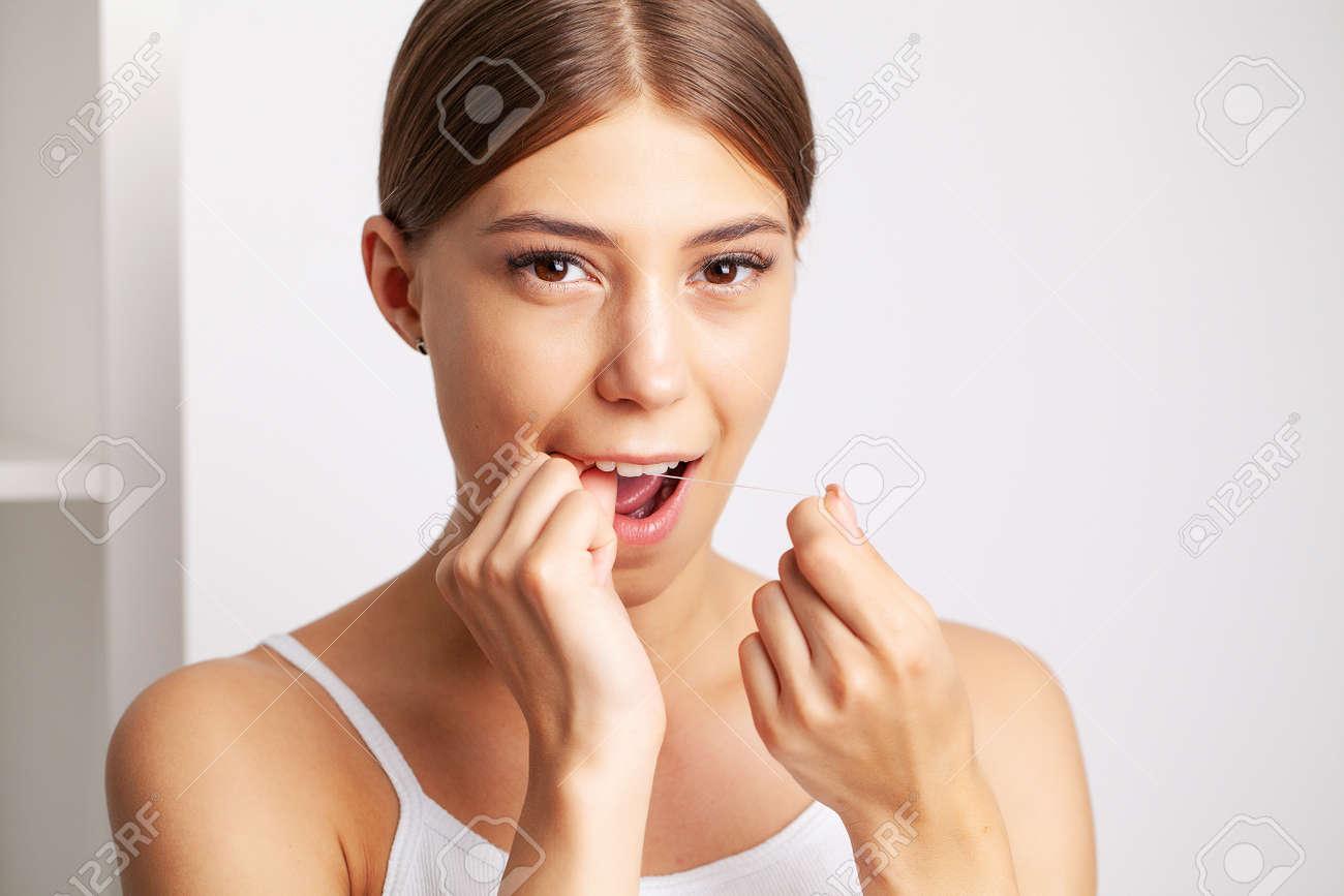 Cheerful brunette woman using dental floss in bathroom - 165697593