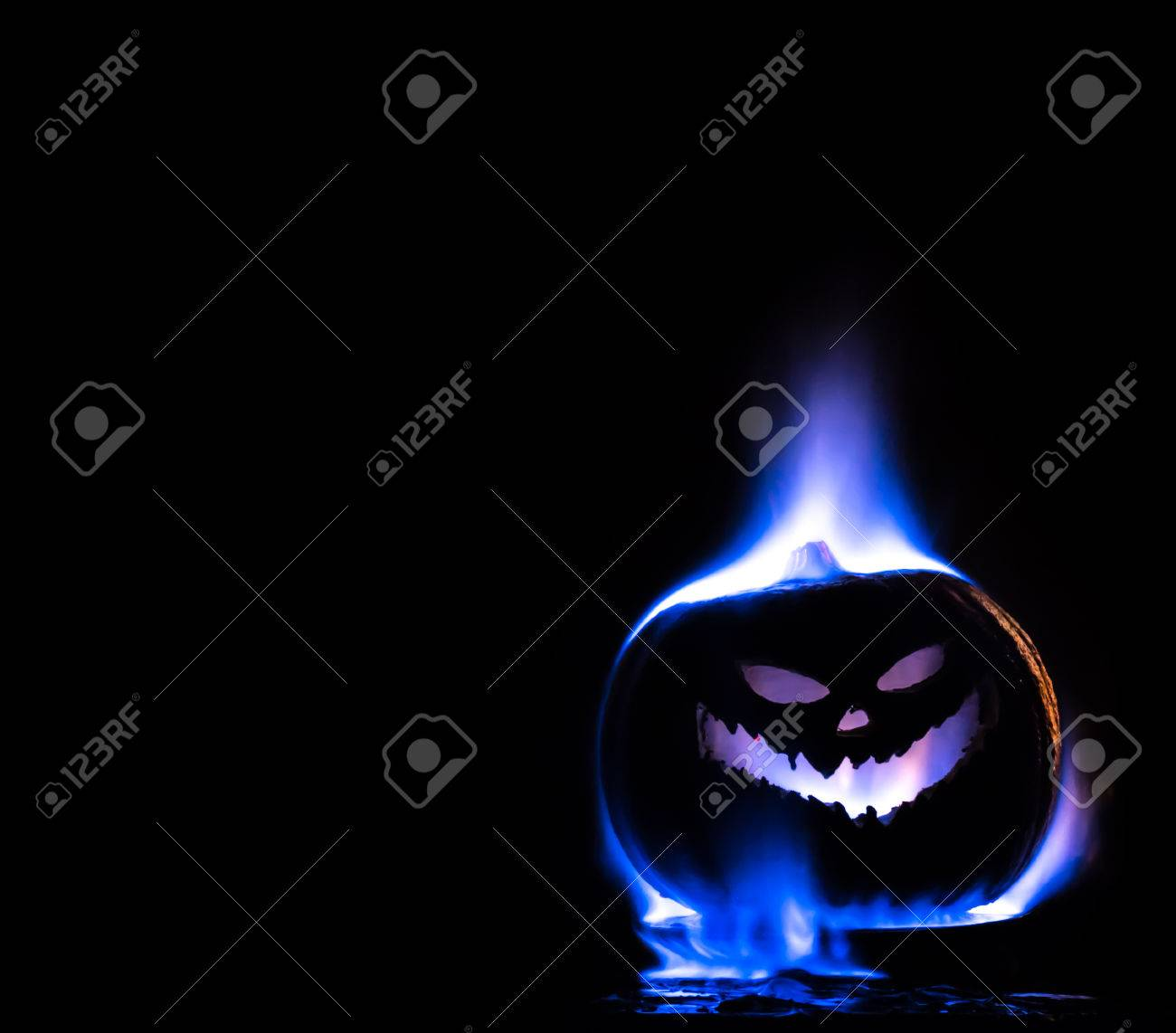 a halloween jack o lantern engulfed in blue flame isolated on