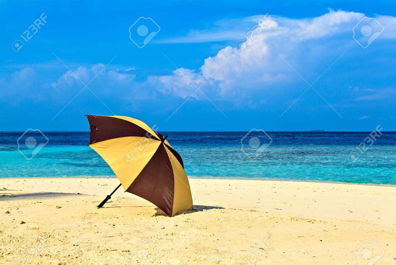 Opened umbrella is on the ocean beach Stock Photo - 19137151