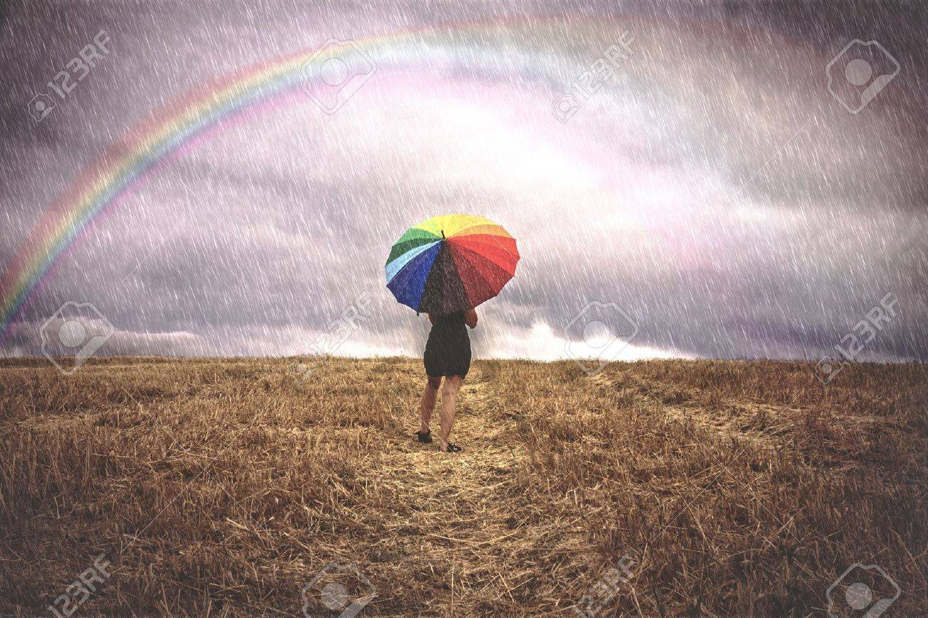 Woman in field with colorful umbrella in the rain - 20622193
