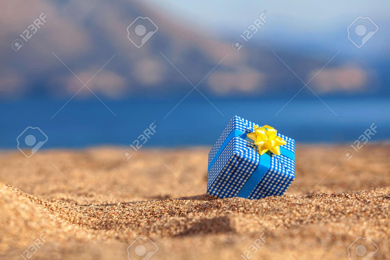 Blue gift box on a beach - 36973615