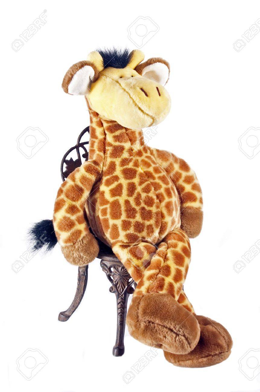 Stock Photo   Toy Giraffe Sitting On Old Garden Chair Isolated On White